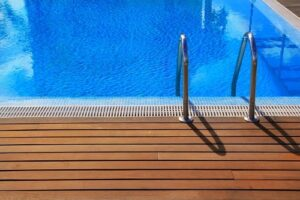 Blue swimming pool with teak wood flooring surrounding.