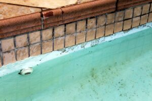 Paint coming off damaged pool that need repair.