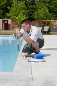 Pool technician performing a chemical test checking chlorine, PH and other chemical levels in swimming pool